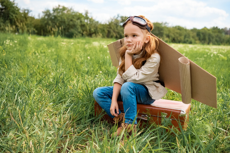 pensive kid in pilot costume sitting on retro suitcase in summer field