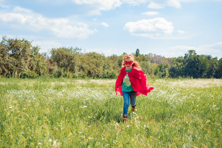 little kid in red superhero cape and mask running in meadow on summer day Stock Photo