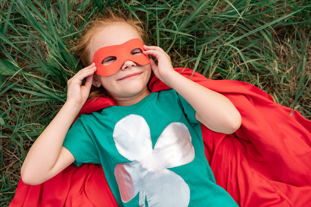 overhead view of kid in red superhero cape and mask lying on green grass Stock Photo