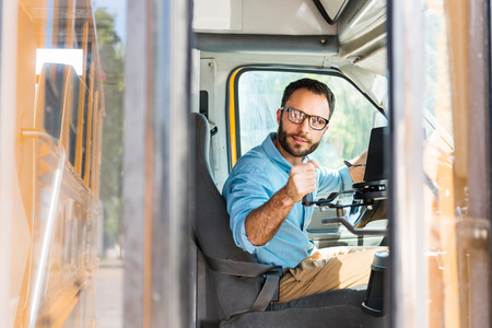 school bus driver losing door with lever and looking back Stockfoto