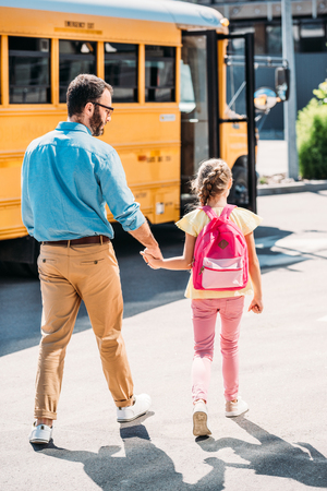 rear view of father and daughter with backpack holding hands and walking to school bus 스톡 콘텐츠