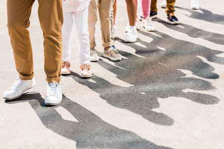 Kurzaufnahme eines Erwachsenen und von Kindern in verschiedenen Schuhen und Hosen, die in einer Reihe stehen
