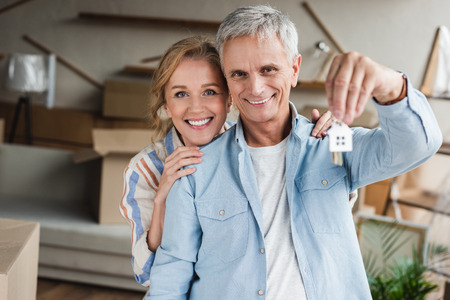 happy elderly couple holding keys from new house and smiling at camera