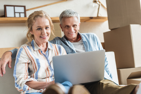 happy senior couple using laptop together during relocation