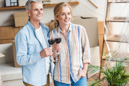 happy senior couple holding glasses of wine and looking away in new house Stockfoto