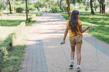 rear view of cute kid holding jumping rope and walking in park Stockfoto