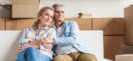 gelukkig bejaarde echtpaar omarmen en wegkijken zittend samen op de bank in een nieuw huis