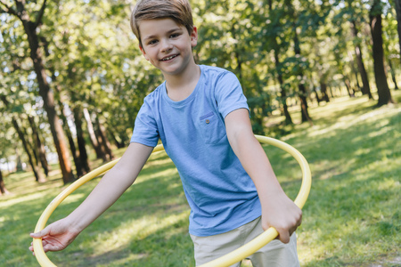happy boy playing with hula hoop and smiling at camera in park Stock Photo