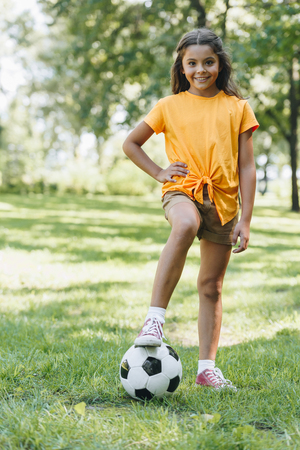 cute happy child standing with soccer ball and smiling at camera in park Foto de archivo - 108155454