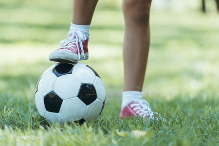 cropped shot of child standing with soccer ball on grass 스톡 콘텐츠