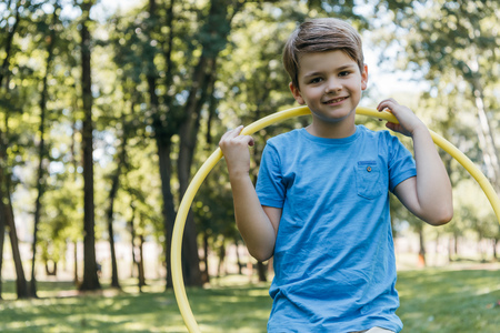 adorable happy boy holding hula hoop and smiling at camera in park Stock Photo