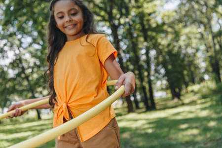 cute smiling child playing with hula hoop in park