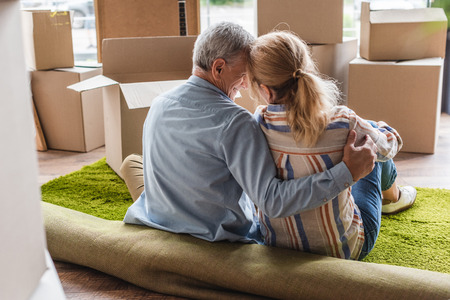 back view of happy senior couple hugging while sitting on carpet in new home Banco de Imagens