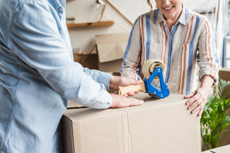 cropped shot of smiling senior couple packing cardboard box during relocation