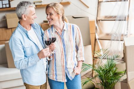 Feliz pareja senior sosteniendo copas de vino y sonriendo durante la reubicación