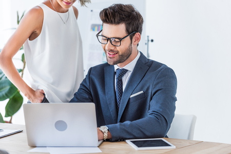 cropped image of young smiling businesspeople looking at laptop in office