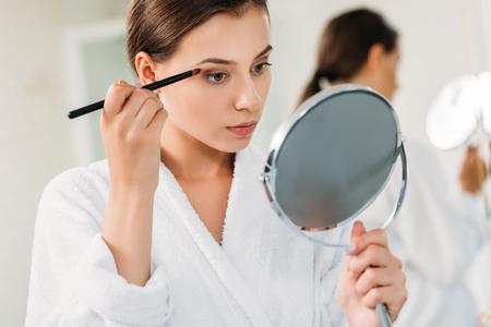 beautiful young woman holding mirror and applying eyeshadow