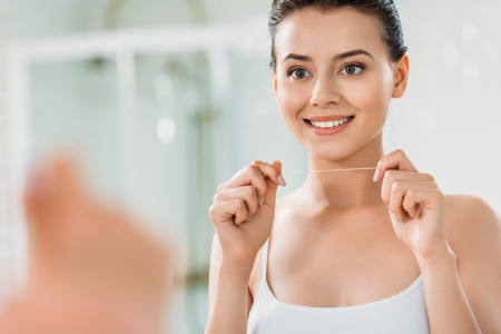 beautiful smiling girl holding dental floss and looking at mirror in bathroom