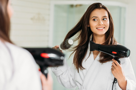 szczęśliwa młoda kobieta, suszenie włosów w lustrze w łazience Zdjęcie Seryjne