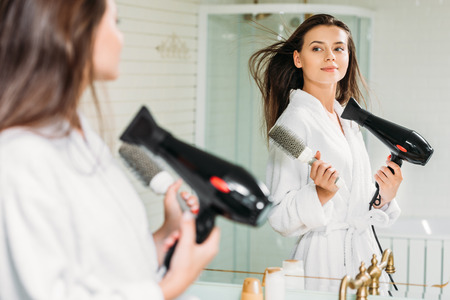 beautiful young woman holding hair brush and drying hair at mirror in bathroom Banque d'images - 108185497
