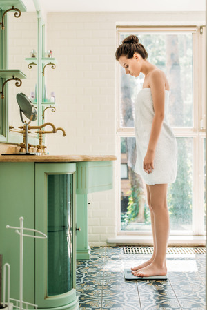 side view of beautiful young woman in towel standing on digital scales in bathroom