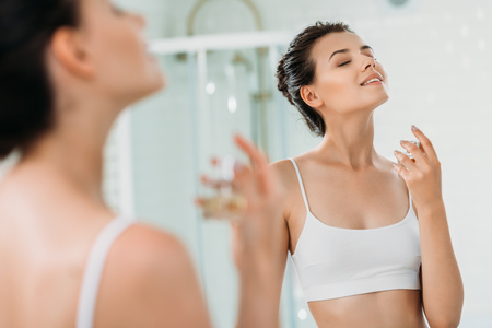 beautiful smiling girl with closed eyes applying perfume at mirror in bathroom