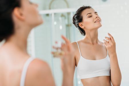 piękna uśmiechnięta dziewczyna z zamkniętymi oczami, aplikująca perfumy w lustrze w łazience