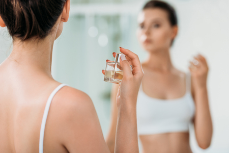 cropped shot of girl applying perfume at mirror in bathroom