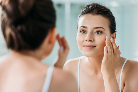 beautiful smiling girl touching face and looking at mirror in bathroom Banco de Imagens