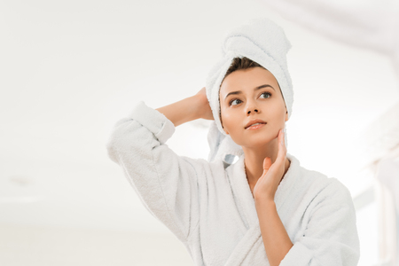 low angle view of beautiful pensive girl in bathrobe and towel on head looking away in bathroom