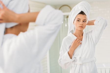 beautiful young woman in bathrobe and towel on head looking at mirror in bathroom