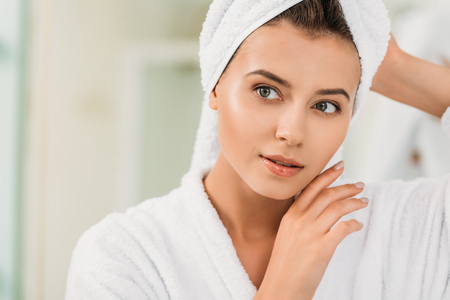 portrait of beautiful young woman in bathrobe and towel on head