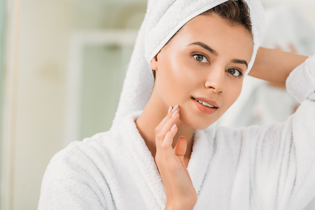 beautiful smiling girl in bathrobe and towel on head looking at camera in bathroom Stock Photo