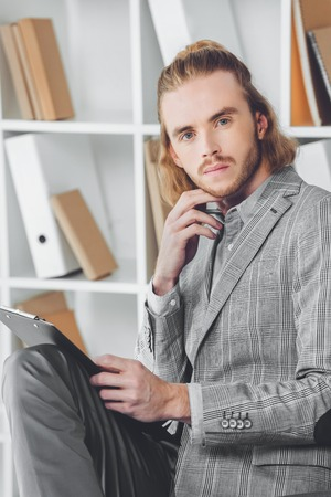 portrait of pensive businessman holding clipboard and looking at camera
