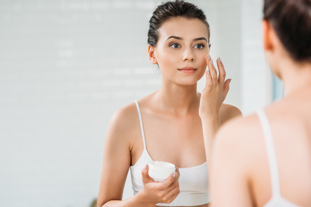 beautiful girl applying face cream and looking at mirror in bathroom Banco de Imagens