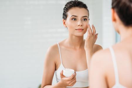 Belle fille appliquant la crème pour le visage et regardant le miroir dans la salle de bain
