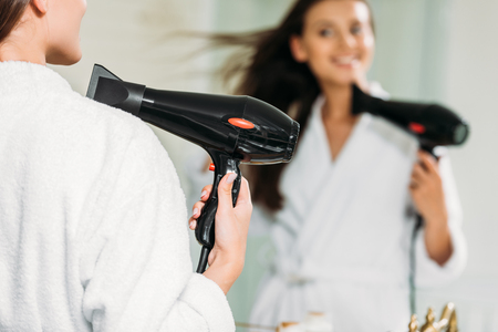 selective focus of smiling girl in bathrobe using hair dryer at mirror in bathroom