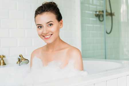 beautiful happy young woman smiling at camera while relaxing in bathtub with foam 版權商用圖片 - 108194400