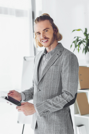 smiling businessman standing with tablet and looking at camera