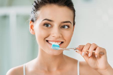 beautiful smiling girl brushing teeth in bathroom Stockfoto