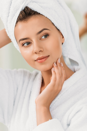 beautiful pensive young woman in bathrobe and towel on head looking away Stock Photo