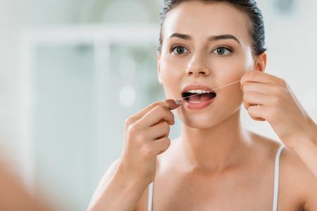 Hermosa joven con hilo dental en el baño. Foto de archivo