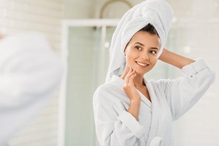 Hermosa joven sonriente en bata de baño y toalla en la cabeza mirando al espejo en el baño. Foto de archivo