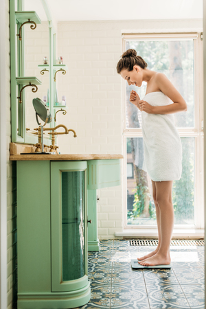 happy young woman in towel standing on digital scales in bathroom