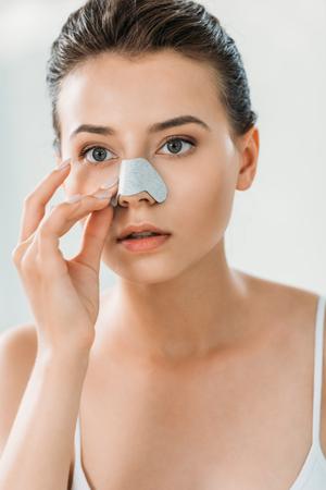 beautiful focused girl applying nose strip in bathroom