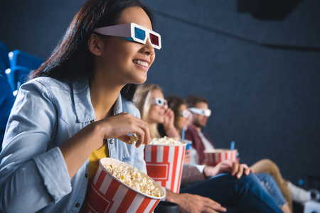 smiling asian woman in 3d glasses with popcorn watching movie in cinema