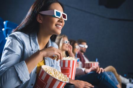 lächelnde asiatische Frau in der 3D-Brille mit Popcorn, das Film im Kino sieht