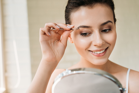 smiling young woman correcting eyebrows with tweezers and looking at mirror 版權商用圖片 - 108199269
