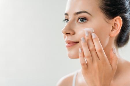 Belle jeune femme souriante, appliquer la crème pour le visage et regarder ailleurs
