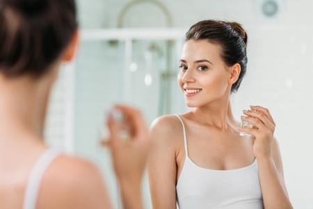 Hermosa joven sosteniendo frasco de perfume y mirando en el espejo en el baño. Foto de archivo